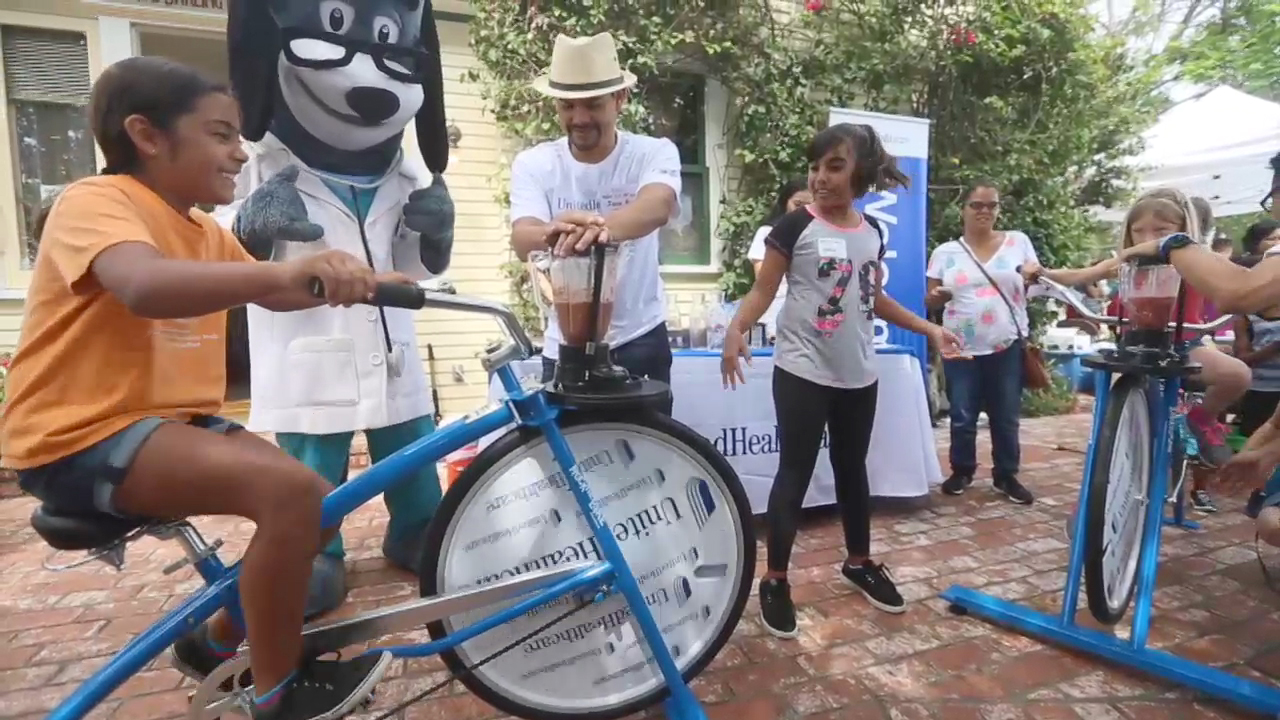 Kids pedal specially made smoothie bikes today at the annual Olivewood Gardens and Learning Center Day of Play in National City, Calif., while UnitedHealthcare mascot Dr. Health E. Hound and employee volunteer Jose Gomez cheer them on. The specially made smoothie bikes are designed to help kids and their families connect an active lifestyle with healthy eating. (Video credit: Sandy Huffaker)
