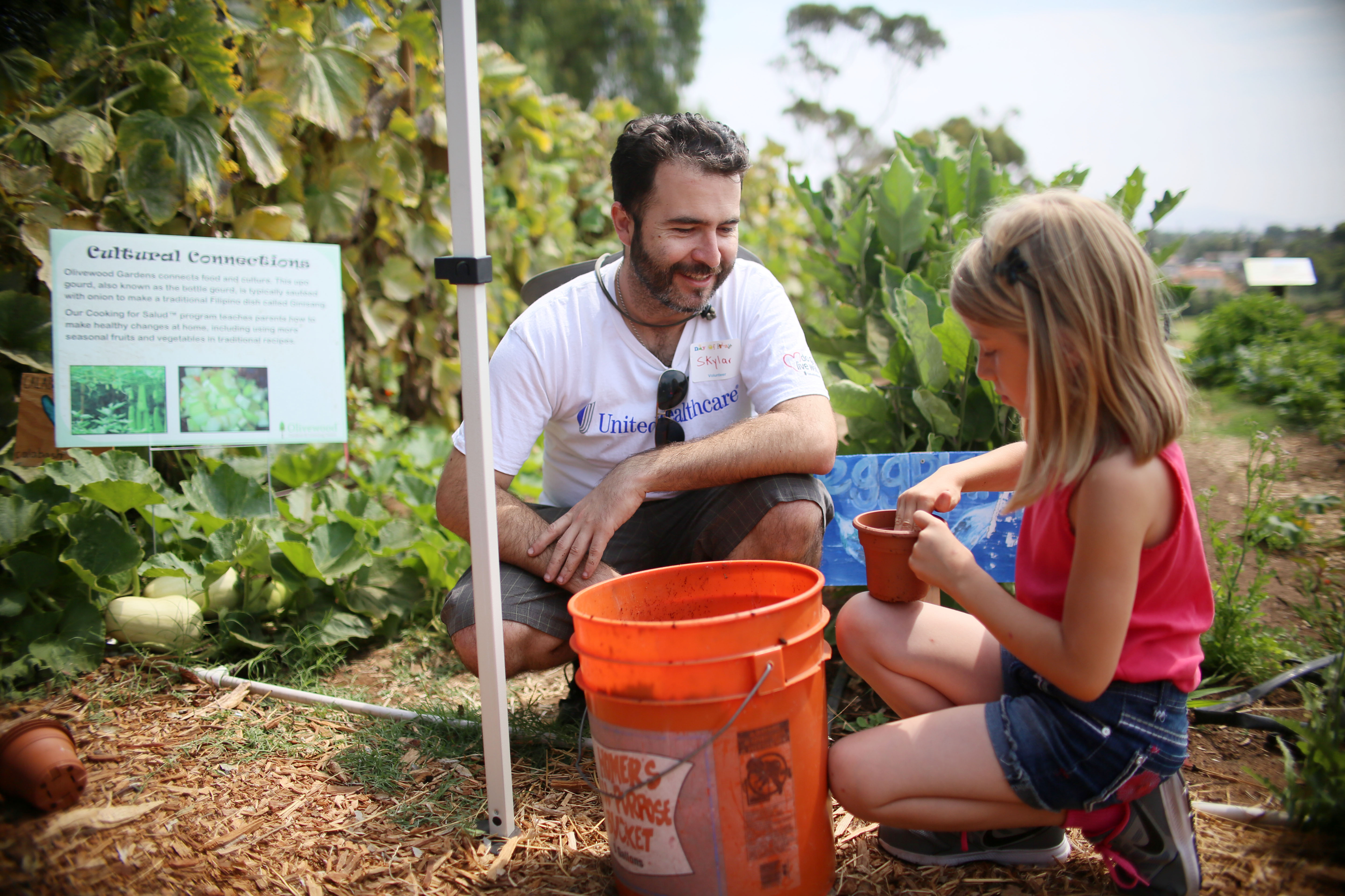 UnitedHealthcare volunteer Skylar Hayes assists Anais with a potted plant activity today at the annual Olivewood Gardens and Learning Center Day of Play in National City, Calif. The Day of Play is a free community festival with hands-on activities related to gardening, physical activity, healthy foods and nutrition for more than 400 San Diego County adults and children. (Photo credit: Sandy Huffaker)