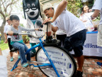 Sarah, left, pedals a specially made smoothie bike today at the annual Olivewood Gardens and Learning Center Day of Play in National City, Calif., while UnitedHealthcare mascot Dr. Health E. Hound and employee volunteer Jose Gomez cheer her on. The specially made smoothie bikes are designed to help kids and their families connect an active lifestyle with healthy eating. (Photo credit: Sandy Huffaker)
