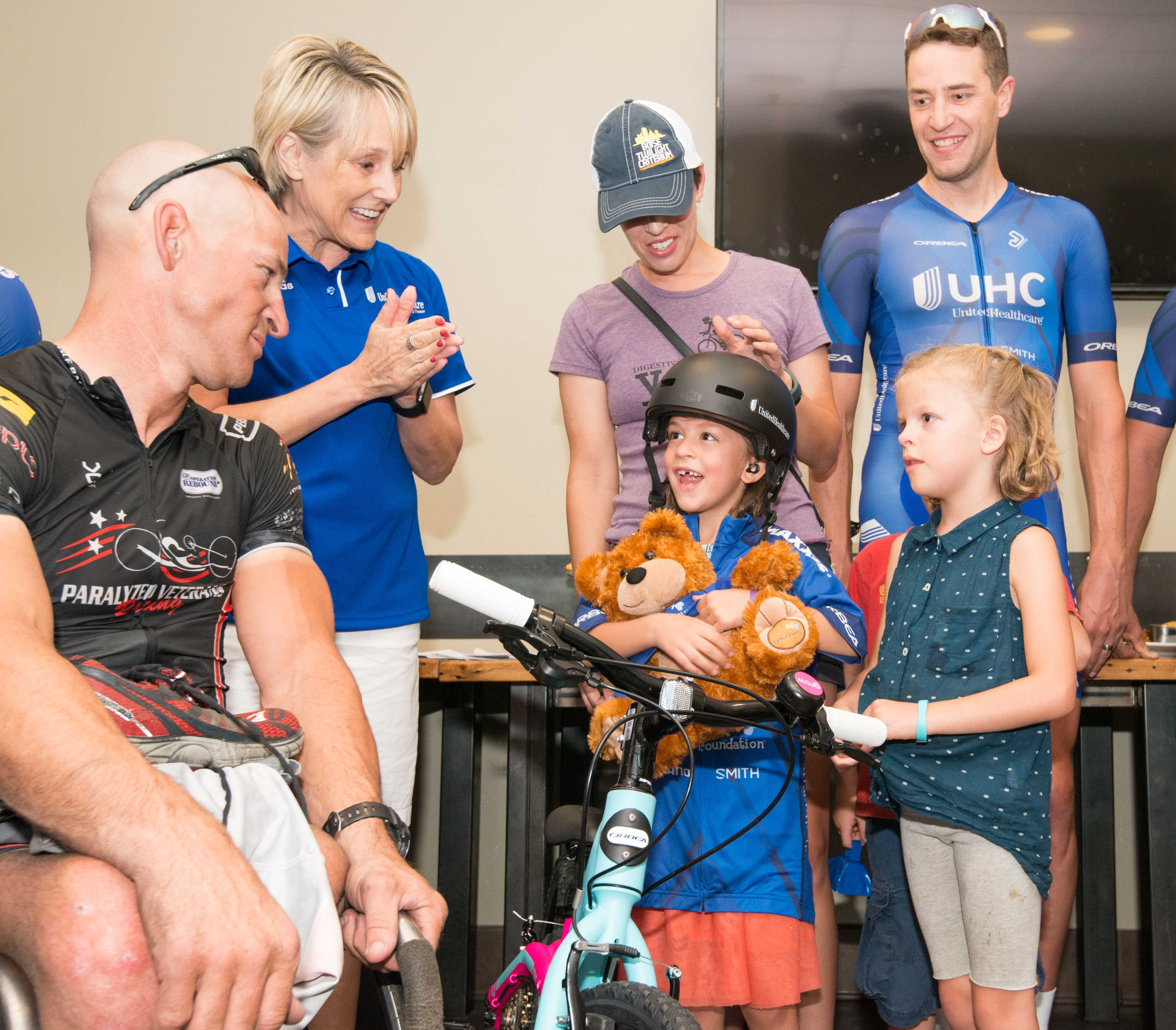 Six-year-old Reagan Cornwall was joined by her sister Ruby and her parents Morgan and Craig when UnitedHealthcare executive Pam Gold and Pro Cycling Team member Adrian Hegyvary surprised her with a brand-new bike, helmet, UHC Pro Cycling team jersey and an opportunity to participate in the cycling event by riding along in the official pace car (Photo: Chad Case Photography).