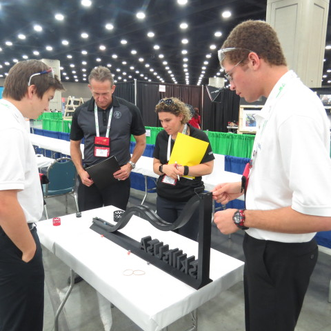 Joshua Martelle and Denver Wiederin, Center for Technology, Essex test their prototype in front of the Additive Manufacturing Competition judges (Photo: Business Wire)