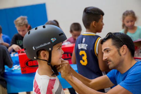 UnitedHealthcare Pro Cycling Team member Sebastian Haedo helps six-year-old Mason Brooks try on his new helmet as part of a bike safety event at the Lied Boys & Girls Club in Salt Lake City today. UnitedHealthcare Pro Cycling Team members and UnitedHealthcare volunteers encouraged kids to be safe, stay active and participate in the upcoming Tour of Utah kids' events. (Photo credit: Kim Raff)