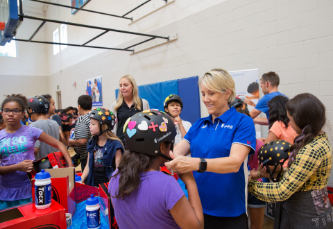 Pam Gold of UnitedHealthcare helps Marissa Medrano, 11, with her new helmet at the Lied Boys & Girls Club in Salt Lake City today. UnitedHealthcare donated 100 helmets to the club to encourage kids to be safe, stay active and participate in the upcoming Tour of Utah kids' events. (Photo credit: Kim Raff)