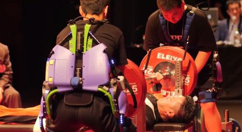 In the experiment, staff who assisted in placing/removing the plates onto/from the bar wore a Power Assist Suit to demonstrate its ability to help lighten the load and to confirm the feasibility of using the suit at actual sports competitions. (Photo: Business Wire)