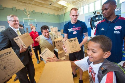 """UnitedHealthcare donated 100 NERF Energy Game Kits to the Boys & Girls Clubs of Boston as part of a national initiative to encourage young people to become more active through """"exergaming."""" L to R: Stephen Farrell, CEO, UnitedHealthcare of New England; Ted Fischer, vice president of business development, Hasbro; Cody Cropper, New England Revolution goalkeeper; and London Woodberry, New England Revolution defender, passed out kits to local youth at the Yawkey Club of Roxbury. A.J., 9, Boys & Girls Clubs of Boston member, is shown receiving a NERF ENERGY Game Kit (Photo: Gretchen Ertl)."""