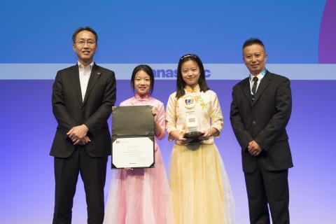 小学生部門グランプリの中国の生徒たちと、パナソニック 竹安執行役員(左)(写真:ビジネスワイヤ)