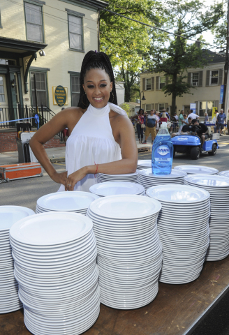 Actress Tia Mowry kicks off the dish washing festivities of over 6,000 dishes with Dawn dish soap to demonstrate how one 21.6 oz bottle of Dawn can clean an entire town's worth of dishes, Sunday, Aug. 13, 2017 in Lambertville, NJ.  (Photo by Diane Bondareff/Invision for Dawn/AP Images)