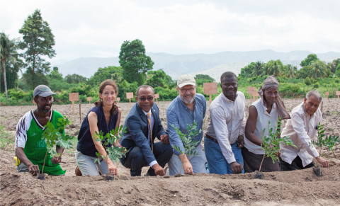 """The Smallholder Farmers Alliance (SFA) and partners plant cotton seeds to reintroduce cotton to Haiti after a 30-year hiatus. Tree seedlings, transplanted elsewhere after the ceremonial planting, symbolize the unique connection between trees and cotton in the SFA/Timberland agroforestry model. Pictured (left to right): Thony Thomas, smallholder farmer; Atlanta McIlwraith, Timberland; Pierre Marie Du Mény, Haitian Minister of Commerce and Industry; Hugh Locke, SFA; Timote Georges, SFA; Nerlande Dautarn, smallholder farmer; Rémillot Léveillé, agronomist who is known as the """"father of cotton"""" in Haiti. Photo credit: SFA/Thomas Noreille."""