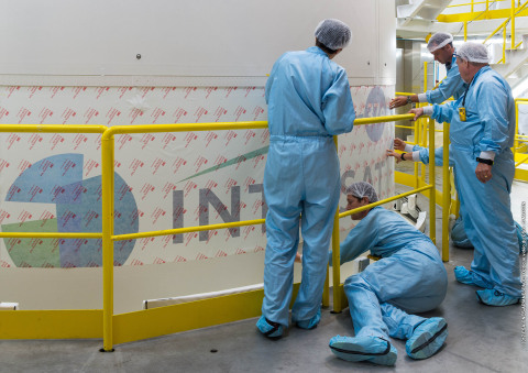 The Intelsat 37e launch team applies the Intelsat logo to the Ariane 5 launch vehicle in preparation ...