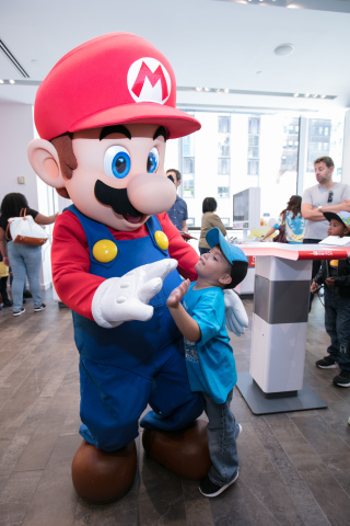 In this photo provided by Nintendo of America, Alessandro A., age 4, from Woodside, NY, greets Mario at the Nintendo NY store during the Nintendo Back-to-School Celebration. (Photo: Business Wire)