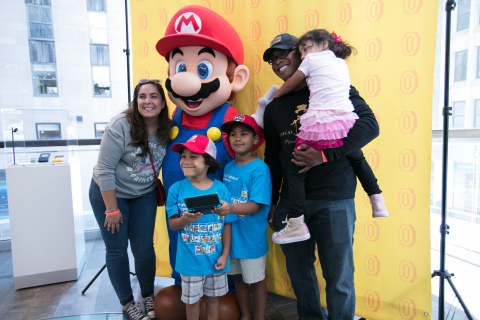 In this photo provided by Nintendo of America, Gemarla G., with her family Glenn, age 5, Gavin, age 7, Grace, age 3, and husband Gary G., from Queens, NY, had their photo taken with Mario at the Nintendo NY store during the Nintendo Back-to-School Celebration.