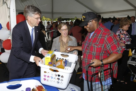 """Congressman Erik Paulsen and Patty Horoho, CEO of OptumServe, UnitedHealth Group's military health services business, present a """"Welcome Home Basket"""" donated by UnitedHealth Group employees to newly moved-in resident Arthur Williams at the ribbon-cutting ceremony for Veterans East, a new 100-unit apartment community for veterans struggling with homelessness (Photo: Greg Page)."""