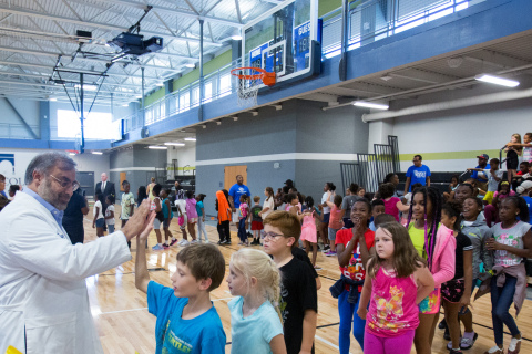 """Dr. Ravi Johar of UnitedHealthcare high-fives Boys & Girls Club of Jefferson City members as they were led through exercises to test out their new NERF ENERGY Game Kits. UnitedHealthcare donated 150 kits as part of a national initiative between Hasbro and UnitedHealthcare, featuring Hasbro's NERF products, that encourages young people to become more active through """"exergaming"""" (Photo: James Schraeder)."""