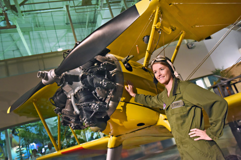 A reenactor portraying historic aviatrix Cornelia Fort poses next to the Museum's Boeing Stearman. (Photo: Business Wire)