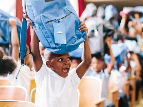 A student happily shows off his book bag of supplies from Kids in Need Foundation. (Photo: Business Wire)