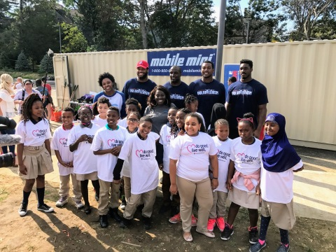 New England Patriots players (L-R) Deatrich Wise, David Harris, Adam Butler and Geneo Grissom huddle with students from Bridge Boston Charter School following today's volunteer project where the athletes worked with volunteers from UnitedHealthcare and nonprofit KaBOOM! to build a playground at Bridge Boston Charter School (Photo: UnitedHealthcare).