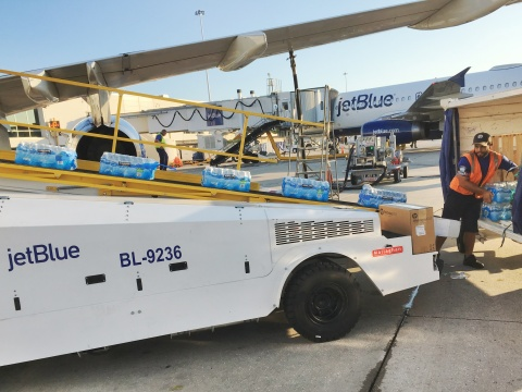 A JetBlue crewmember in Orlando loads relief supplies onto a humanitarian flight to St. Maarten. (Photo: Business Wire)