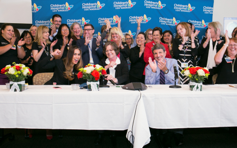 CHLA President and CEO Paul S. Viviano (seated, center) celebrates with staff upon hearing the news ...