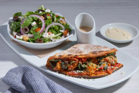 California Pizza Kitchen's Smashed Chicken Meatball Piadina, a folded pizza-style sandwich made with housemade chicken meatballs, crushed tomato sauce, baby kale, fresh herb gremolata and Parmesan mustard aioli. Photo Credit: California Pizza Kitchen