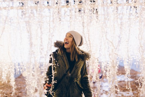 Woman enjoying holiday lights at Enchant Christmas and what holiday revelers can expect at Globe Life Park in Arlington, Texas. (Photo: Business Wire)