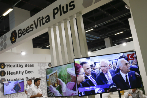TV monitor displays video of Healthy Bees, LLC. news conference with Turkish Agriculture Minister Ahmet Eşref Fakıbaba, PhD (right-moustache) and Philip McCabe, (left-white hair) president, International Federation of Beekeepers' Associations, talking with reporters Bryan Glazer and Elif Ural at BeesVita Plus exhibit, 45th annual Apimondia International Apiculture Congress, Istanbul, Turkey. (Source: Bryan Glazer / World Satellite Television News)