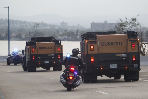 A Puerto Rico Police motorcyclist escorts two Duracell PowerForward vehicles on a Puerto Rico highway to distribute more than $1 million worth of batteries for disaster relief on Thursday, Oct. 12, 2017, in San Juan, Puerto Rico. (Ricardo Arduengo/AP Images for Duracell)