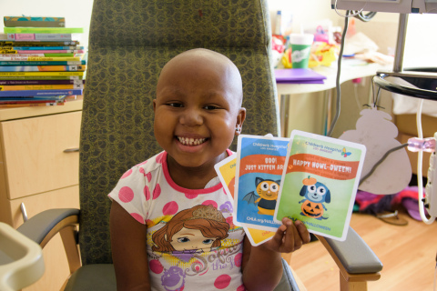 CHLA patient Nzinga Thomas happily shows off the Halloween cards supporters can send to patients from October 20-31 at CHLA.org/Halloween. (Photo: Business Wire)