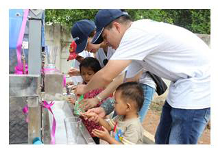 Children in Indonesia with Watts volunteers enjoy clean drinking water from the Aqua Tower installed at their school (Photo: Business Wire)