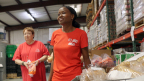 Contina Woods, foreground, is dedicated to using her success to help others succeed. Here, she is photographed volunteering at Prodisee Pantry in Spanish Fort, Ala., near Mobile. (Photo: Business Wire)