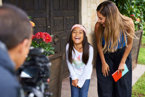 """Photographer Theresa Balderas and Daniela 'Paty' Patricia laugh together during a photo shoot for the """"Dream Big, Princess"""" photo campaign. (Photo: Business Wire)"""