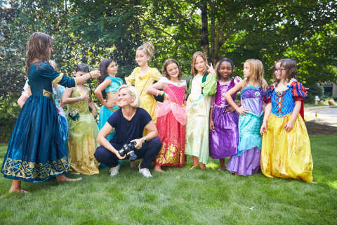 "Photographer Kate T. Parker poses with girls from youth soccer team, The Blasters, during a shoot for the ""Dream Big, Princess"" photo campaign. (Photo: Business Wire)"