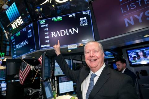 Radian CEO Rick Thornberry points to the company's logo on the New York Stock Exchange trading floor ...