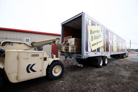 A group of Marines unload a truck full of books, toys and games donated by Barnes & Noble to Toys fo ...
