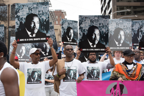 """Advocates participate in Atlanta's 2017 MLK parade and hold up AHF's """"AIDS Is A Civil Rights Issue""""  ..."""
