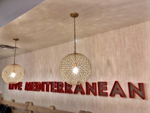"Custom artwork through the restaurant, including signature branding messaging such as ""Live Mediterranean"" that's executed in large red channel letters on the main wall. (Photo: Business Wire)"