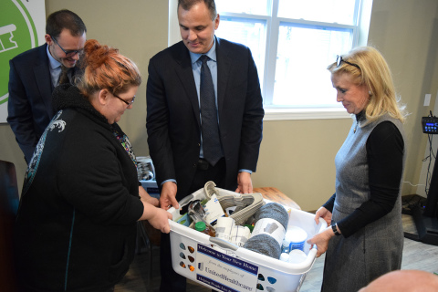 """New Parkridge resident Tiffany LeBlanc receives a """"welcome basket"""" from (L-R) Dennis Mouras, CEO, UnitedHealthcare Community Plan of Michigan and U.S. Congresswoman Debbie Dingell (MI-12); in background, Zachary Fosler, executive director, Ypsilanti Housing Commission. UnitedHealthcare, which is the largest investor in New Parkridge, donated welcome baskets filled with household items and healthy foods to each new resident (Photo: Nick Azzaro)."""