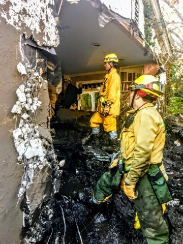 Firefighters lend a hand to the Grokenberger family who returned to their Montecito home in search of personal items following the January 9 mudslides. The residence is a total loss after a 5-foot mudflow slammed through the north wall of their two-story home, filling the first-floor to the top of the front doorway. (Photo: Business Wire)