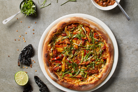 "Created by California Pizza Kitchen's 2017 ""Pizza Chef of the Year,"" CPK's new Citrus Adobo Pizza features slow-cooked pork carnitas tossed in housemade ancho chili adobo sauce, with sweet white corn, roasted peppers, quesadilla and Monterey Jack cheeses, fresh cilantro and lime, served with a side of spicy chili de arbol salsa. (Photo: California Pizza Kitchen and Waterbury Publications)"