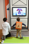 In this photo provided by Nintendo of America, a kid controls a giant, on-screen robot while wearing the Toy-Con Robot suit at an exclusive event in New York on Feb. 2, 2018. The Nintendo Labo Robot Kit launches in stores on April 20, and includes all the parts to build a DIY robot suit. Nintendo Labo kits offer interactive build-and-play experiences designed to inspire creativity and discovery.