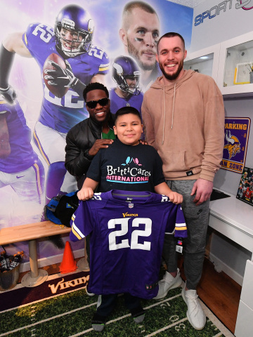 """Minnesota boy battling cancer gets a surprise visit from comedian Kevin Hart and Vikings safety Harrison Smith at the unveiling of his football-themed """"Imagine Me"""" bedroom makeover by BrittiCares and Rally Health on Feb 3. Here, Kevin Hart, Harrison Smith and Andrew Rojas smile for the camera. Photo credit: Getty Images."""