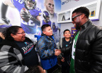 """Minnesota boy battling leukemia gets a surprise visit from comedian Kevin Hart at the unveiling of his football-themed """"Imagine Me"""" bedroom makeover from nonprofit BrittiCares and digital health company Rally Health on Feb 3. Here, Kevin Hart greets Andrew and the Rojas family. Photo credit: Getty Images."""