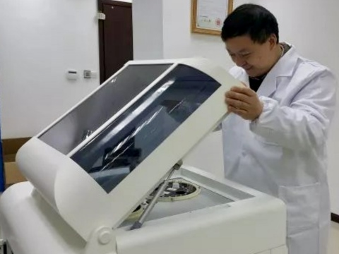 """Anpac Bio-Medical Science Company CEO Dr. Chris Yu inspects one of the company's proprietary """"Cancer Differentiation Analysis"""" (CDA) liquid biopsy technology devices before screening simple, standard blood tests signals of early disease. Anpac Bio's CDA technology consistently detects 26+ cancers, with a 75%-90% sensitivity/specificity rates, usually identifying the disease at its earliest stages. And it does so without any harmful side effects in patients; generating far fewer """"false positives""""; at a cost substantially lower than traditional testing; and generating results within minutes of sample submission. Fully-commercialized with 200 patents filed worldwide, Anpac Bio and its respected medical research partners are celebrating #NationalCancerPreventionMonth by surpassing a new global milestone: processing 60,000+ independently-corroborated CDA tests for early cancer screening and detection; as well as monitoring cancer treatment, effectiveness, and recurrence. (Photo: Business Wire)"""