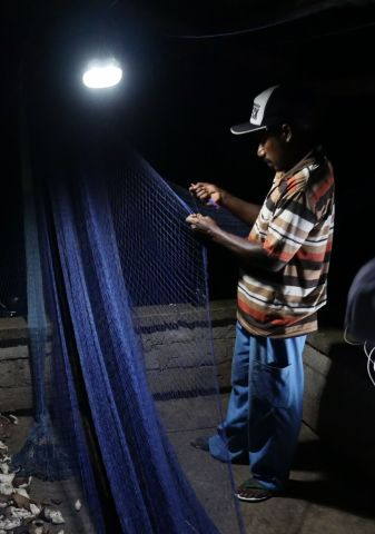 捐赠的太阳能灯助力夜间修补渔网,从而提高渔业生产力。(照片:美国商业资讯)