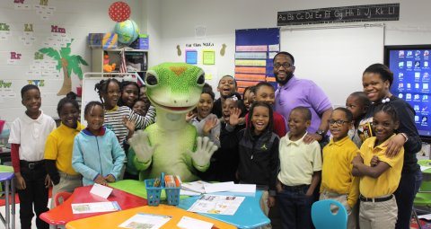 GEICO associate Dennis White joins the Gekco in posing with Quantesha Pittman and her second-graders. Last month, White was a volunteer teacher for the class. (Photo: Ryan McKinney)