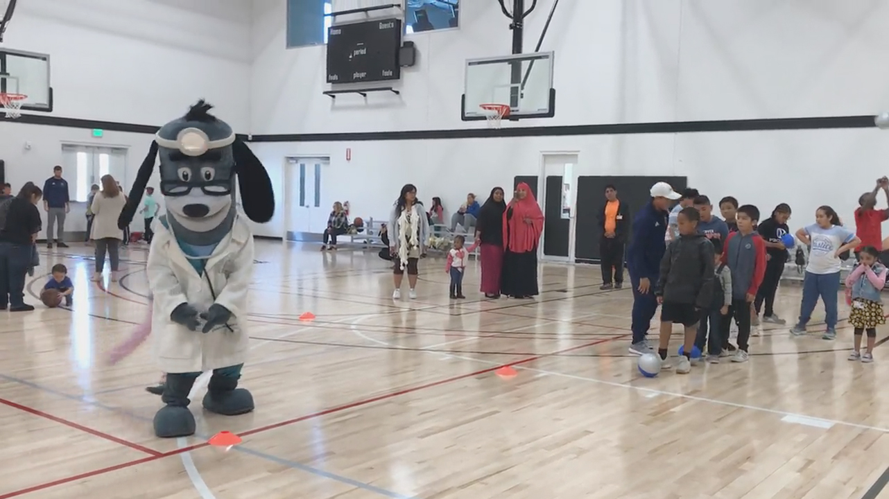 """UnitedHealthcare donated 150 NERF ENERGY Game Kits to the Jackie Robinson Family YMCA as part of a national initiative to encourage young people to become more active through """"exergaming."""" Ze Roberto, San Diego Sockers defender, and UnitedHealthcare mascot Dr. Health E. Hound, led members through exercises to test their new NERF ENERGY Game Kit that tracks activity earning """"energy points"""" in order to play the game (Video: Anita Sen)."""
