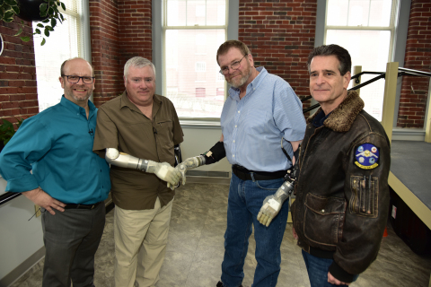 Pictured left to right: Matt Albuquerque of Next Step Bionics & Prosthetics, Chuck Hildreth, Ron Currier and Dean Kamen of DEKA Research & Development. Ron, the first-ever bilateral amputee to be fitted with two LUKE Arms shakes hands with Chuck who is using a LUKE arm featuring a fully integrated powered shoulder, elbow, wrist and hand.