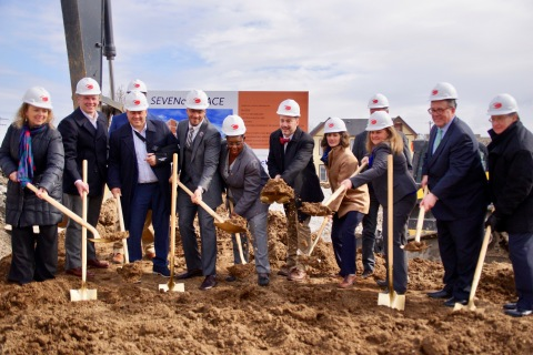 Community leaders and development partners don hard hats and shovels for a groundbreaking ceremony c ...