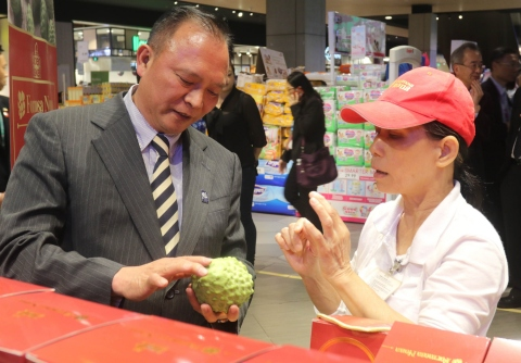 Council of Agriculture Minister Lin Tsung-hsien (left) introduces atemoya to a local staff during a visit to a supermarket on Saturday as part of his two-day trip to Malaysia. (Photo: Business Wire)