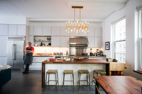 """Chef Wylie Dufresne's kitchen renovation features a large walnut island for entertaining and food prep, rich brass stools and a grand stainless steel 42"""" True Residential Refrigerator. (Photo: Business Wire)"""