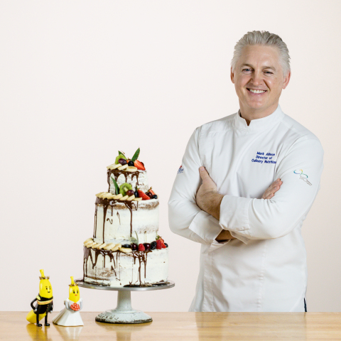 """Dole's Executive Chef Mark Allison with a preview of the banana-inspired """"groom's cake"""" offered to Prince Harry for his May 2018 wedding to Meghan Markle (Photo: Business Wire)"""